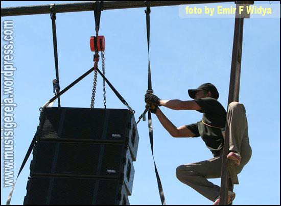 Rekan Luki sedang mengangkat bagian belakang line array dengan mengubah ketegangan tie down ratchet